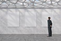 Homme d'affaires regardant à l'affiche trois Photos stock