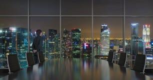 Homme d'affaires regardant à la ville de nuit Photo stock