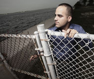 Homme d'affaires regardant au-dessus d'une frontière de sécurité Photo stock