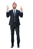 homme d'affaires regardant en haut avec des doigts croisés Photos stock