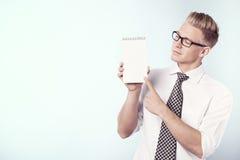 Homme d'affaires regardant et dirigeant le doigt le bloc - notes vide. Photos libres de droits