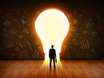 Homme d'affaires regardant l'ampoule lumineuse dans le mur Photos stock