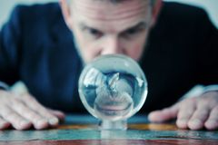 Homme d'affaires regardant la boule en verre sur la table Photos stock