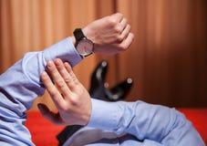 Homme d'affaires regardant la montre-bracelet et se trouvant sur le lit Images stock