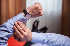 Homme d'affaires regardant la montre-bracelet et se trouvant sur le lit Image libre de droits