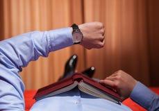 Homme d'affaires regardant la montre-bracelet et se trouvant sur le lit Photos libres de droits
