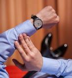 Homme d'affaires regardant la montre-bracelet et se trouvant sur le lit Image stock