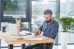Homme d'affaires regardant la montre sur le poignet tout en se reposant sur le lieu de travail avec l'ordinateur portable Photo stock
