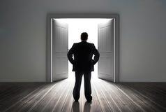 Homme d'affaires regardant la porte montrant la lumière lumineuse photographie stock libre de droits