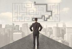 Homme d'affaires regardant la route avec le labyrinthe et la solution Photo stock