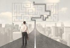 Homme d'affaires regardant la route avec le labyrinthe et la solution Photographie stock libre de droits