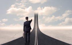 Homme d'affaires regardant la route 3d qui entre dans le ciel Photo stock