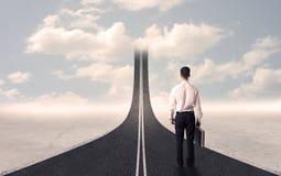 Homme d'affaires regardant la route 3d qui entre dans le ciel Photographie stock
