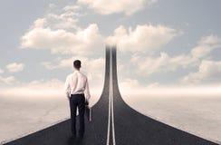 Homme d'affaires regardant la route 3d qui entre dans le ciel Photographie stock libre de droits