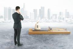 Homme d'affaires regardant la souricière à clapet avec l'argent Photo stock