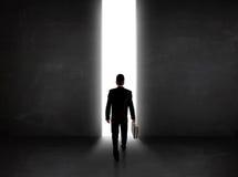 Homme d'affaires regardant le mur avec l'ouverture légère de tunnel Photographie stock libre de droits