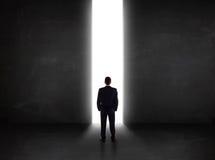 Homme d'affaires regardant le mur avec l'ouverture légère de tunnel Image stock