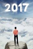 Homme d'affaires regardant le numéro 2017 sur le ciel Photo stock