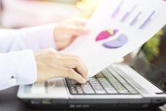 Homme d'affaires regardant le papier de graphique des finances, du compte et des affaires photos stock