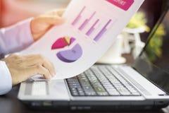 Homme d'affaires regardant le papier de graphique des finances, du compte et des affaires avec le carnet images stock
