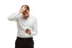 Homme d'affaires regardant le téléphone tenant la tête Photos stock