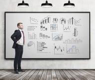 Homme d'affaires regardant les graphiques multiples Image stock