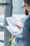 Homme d'affaires regardant les papiers blancs dans des mains dans le bureau Photographie stock