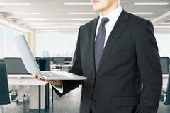 Homme d'affaires regardant He ordinateur portable dans le bureau moderne de l'espace ouvert Image stock