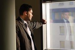 Homme d'affaires regardant par des abat-jour d'hublot Photographie stock