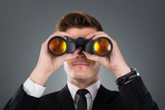 Homme d'affaires regardant par des jumelles Images stock
