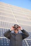 Homme d'affaires regardant par des jumelles devant les panneaux solaires Image stock