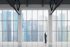 Homme d'affaires regardant par la fenêtre dans le bureau photographie stock