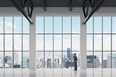 Homme d'affaires regardant par la fenêtre dans le bureau images stock