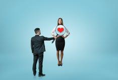 Homme d'affaires regardant par le woman& x27 ; coffre de s avec la loupe et de voir le coeur à l'intérieur Photos libres de droits
