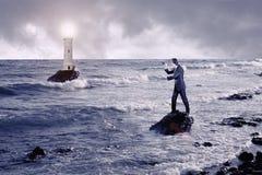 Homme d'affaires regardant par un télescope contre la mer orageuse avec le phare photos libres de droits