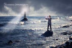 Homme d'affaires regardant par un télescope contre la mer orageuse avec le phare photos stock