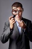 Homme d'affaires regardant par une loupe photographie stock libre de droits