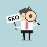 Homme d'affaires regardant par une loupe avec SEO Sign Image libre de droits
