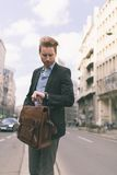 Homme d'affaires regardant sa montre-bracelet dans une ville occupée image stock