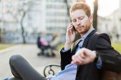 Homme d'affaires regardant sa montre un jour ensoleillé en parc de ville photos stock
