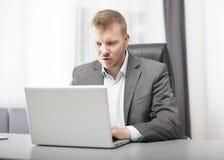 Homme d'affaires regardant son ordinateur portable dans l'incrédulité Photo libre de droits