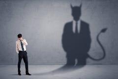 Homme d'affaires regardant son propre concept d'ombre de démon de diable photographie stock