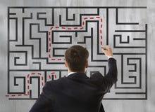 Homme d'affaires regardant un labyrinthe Image stock