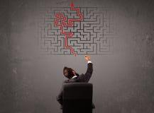 Homme d'affaires regardant un labyrinthe et la sortie Photographie stock libre de droits
