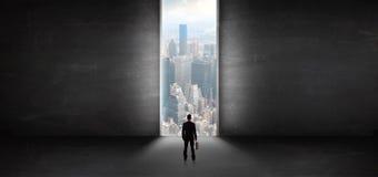 Homme d'affaires regardant ? un paysage urbain d'une salle vide sombre image stock
