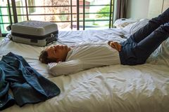 Homme d'affaires Relaxing On Bed dans la chambre d'h?tel photo libre de droits