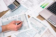 Homme d'affaires remplissant feuille d'impôt 1040 d'ordinateur portable d'aide Photo libre de droits