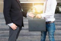 Homme d'affaires remplissant serviette noire pour échanger l'affaire de transfert photos stock