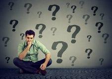 Homme d'affaires reposant sur un plancher avec beaucoup de questions ce qui à faire après Images stock