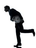 Homme d'affaires retenant l'horloge volant la silhouette de temps Image libre de droits